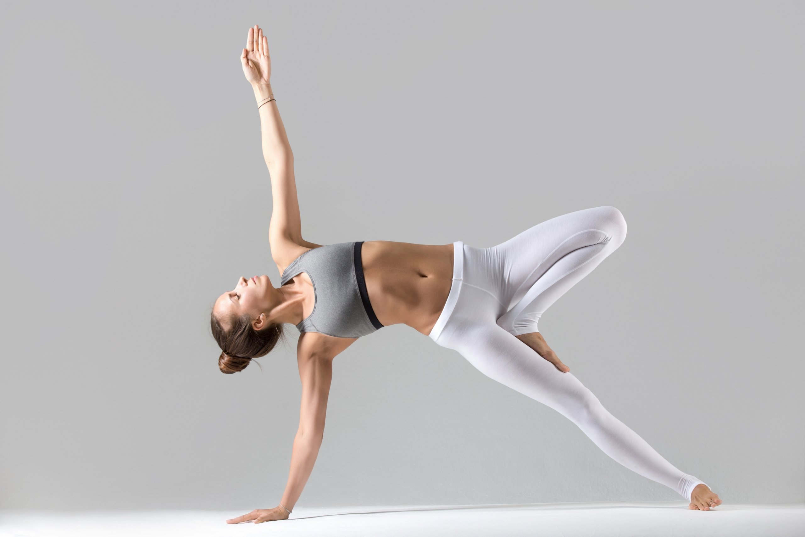 Young woman side plank pose grey studio background scaled - wondercise | online fitness academy | official website